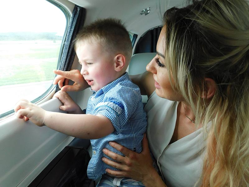 mother-and-son-looking-out-window-of-private-charter-flight